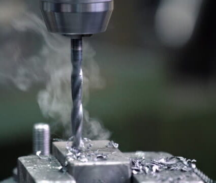 Closeup of steel drill making a hole in a roughly processed piece of metal that requires further processing. There is scrap metal and smoke due to intensive heat. 4k video, static.